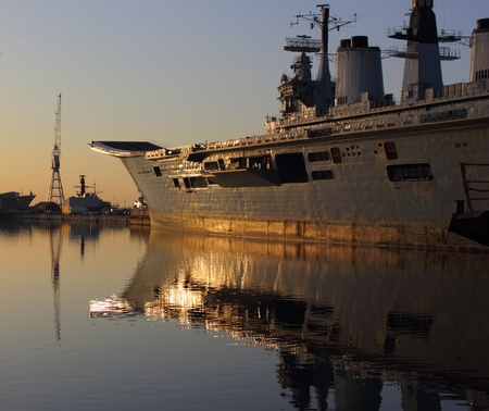 An old aircraft carrier during late evening being reflected in the water by the late sun