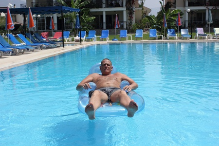 All alone in a hotel swimming pool with no one else in view with the empty sunbeds  Stock Photo