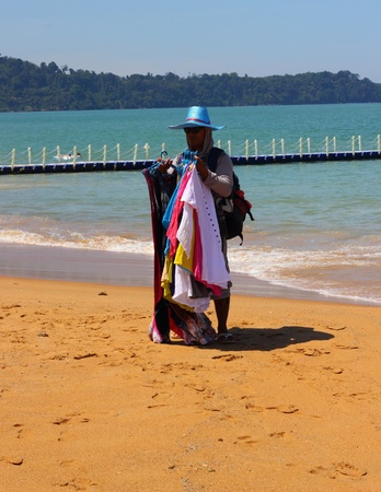 A young male beach trader selling his goods along the beach of Khao Lak in Thailand looking very colorful