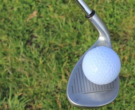 A golf ball balanced on a sandwedge golf club photo
