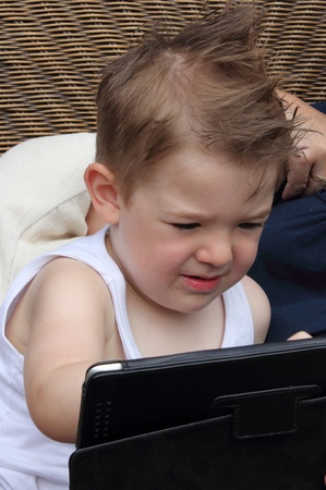 A young boy of two using a computer tablet photo