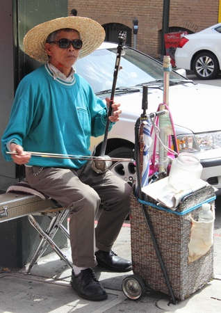 Old asian man playing musical instrument in Chinatown, San Francisco,march 2013