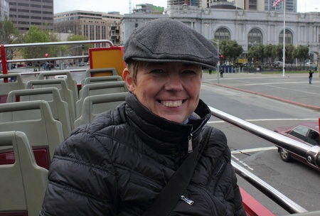 Mature lady wearing a coat and flat cap ,trying to keep warm while sitting on a bus photo
