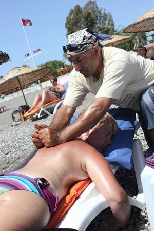 Masseur giving a full body oil massage to a beautiful mature woman on the beach at calis in Turkey on the 30th May 2013 Stock Photo - 20188564