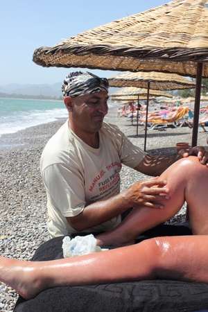 Masseur giving a full body oil massage to a beautiful mature woman on the beach at calis in Turkey on the 30th May 2013