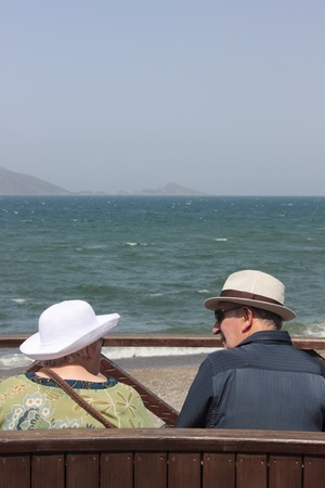 An elderly couple wearing hats and relaxing along the coast of Calis, Turkey, 3rd june 2013