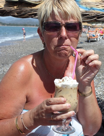 Blonde lady drinking an iced coffee on calis beach in Turkey  photo