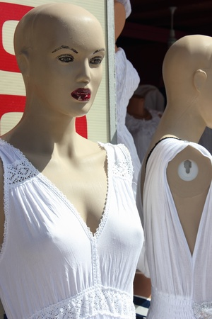 Two mannequins dressed in a white summer dress photo