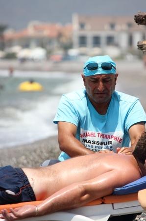 TURKEY, CALIS,  20th July 2013 -  A male  having a massage on a beach