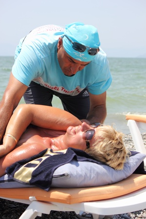 Masseur giving a full massage to a beautiful mature woman on the beach at calis in Turkey on the 30th May 2013