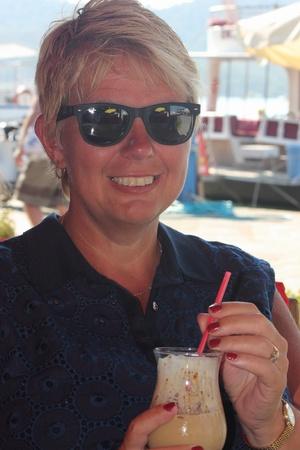 A woman enjoying a drink wearing sunglasses photo