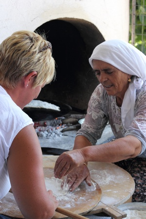 TURKEY,CALIS, 1st AUGUST 2013 - Old Turkish ladies making traditional turkish bread and pancakes and teaching an english lady how to do it herself