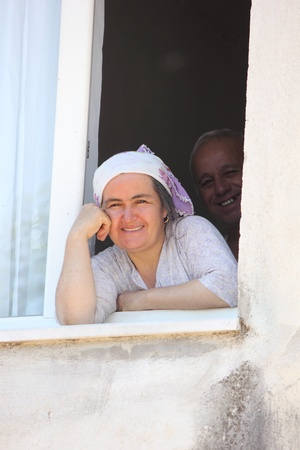 old couple smiling and looking out of a window of a house in an old village in Turkey,2013