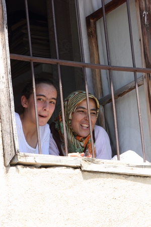Young smiling Turkish females looking out of a window of a house in turkey,2013