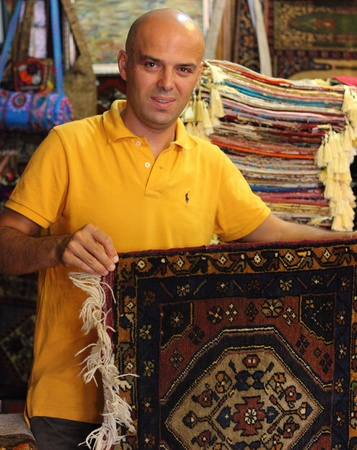 Local trader with his textiles ,rugs and fabrics for sale in his old traditional shop, Fethiye, Turkey, 2013 Editorial