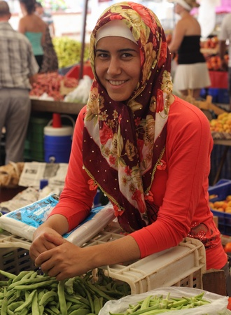 A pretty woman selling her fruit and vegetables at a local market in Turkey, July  2013