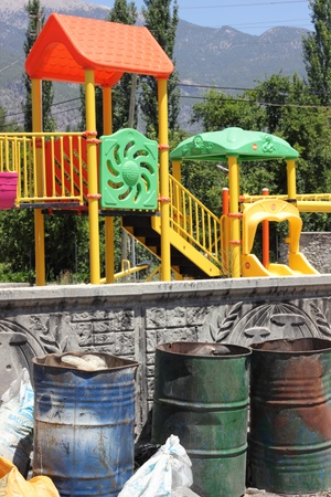 A childrens playground with dangerous waste containers nearby photo