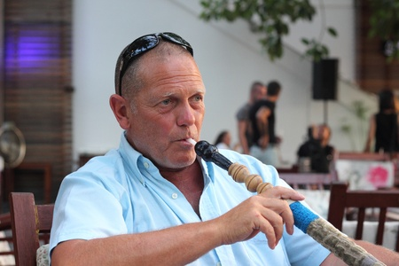 A portrait of a man smoking a hookah waterpipe in a Turkish bazaar photo