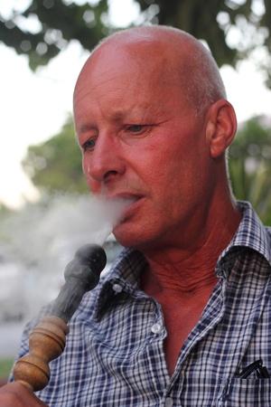 A portrait of a man smoking a hookah waterpipe in a Turkish bazaar