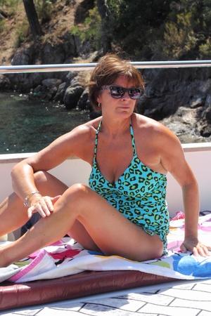 donne mature sexy: Una signora di relax al sole sul ponte di una barca