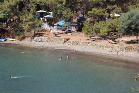A beautiful view of Katranci bay with  swimmers and a campsite near Calis in Turkey, August 2013 photo