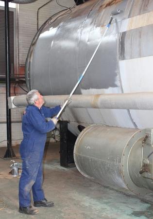 An engineer painting an industrial steam boiler Standard-Bild