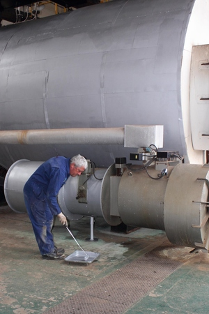 An engineer painting an industrial steam boiler Stock Photo