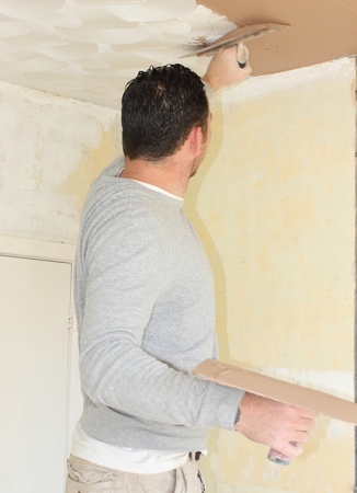 skimming: PORTSMOUTH, ENGLAND, 14th SEPT 2013   A plasterer plastering over an artexed ceiling for a smooth finish