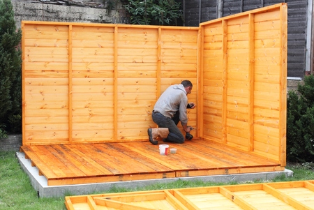 Building a wooden shed and fixing the panels together and to the base Stock Photo