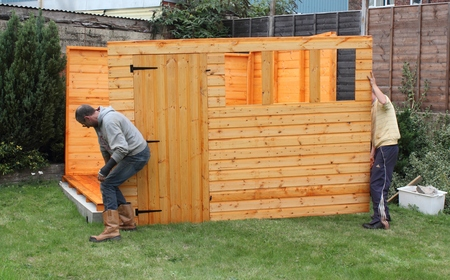 Building a wooden shed and fixing the panels together and to the base Standard-Bild