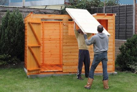 Het bouwen van een houten schuur en zetten het dak in positie