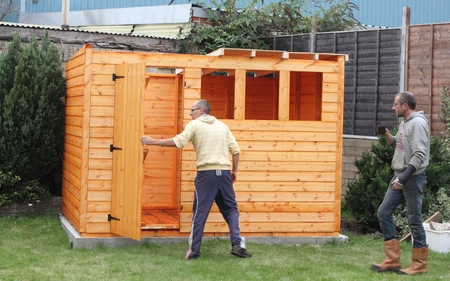 Building a wooden shed and putting the roof in position Standard-Bild