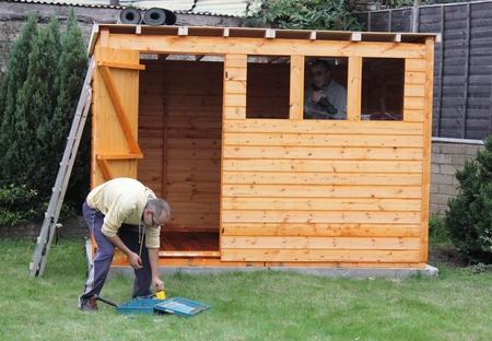 Building a wooden shed and laying the felt on the roof to make waterproof