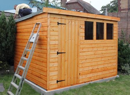 Het bouwen van een houten schuur en tot het vilt op het dak waterdicht maken