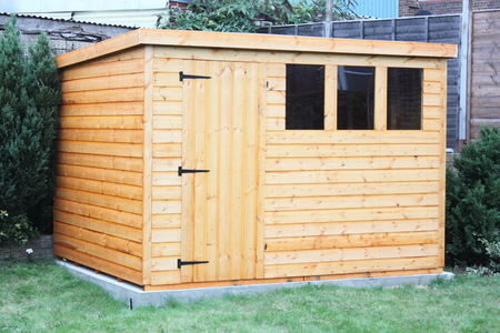 A newly built wooden garden shed sitting on a concrete base Stock Photo