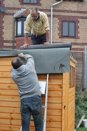 Building a wooden shed and laying the felt on the roof to make waterproof photo