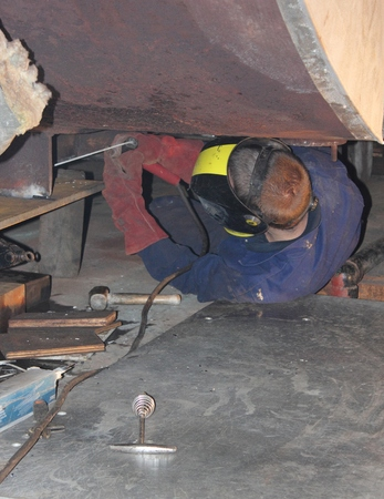 A welder welding new support plates on the botom of a 40,000lb duel fuel steam boiler after rust and decay found during refit  Redakční
