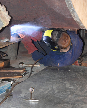 A welder welding new support plates on the botom of a 40,000lb duel fuel steam boiler after rust and decay found during refit