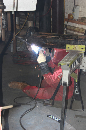 A welder welding a flange onto a pipe for a repair on a steam boiler in the background Stock Photo