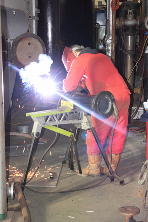 A welder welding a flange onto a pipe for a repair on a steam boiler in the background photo