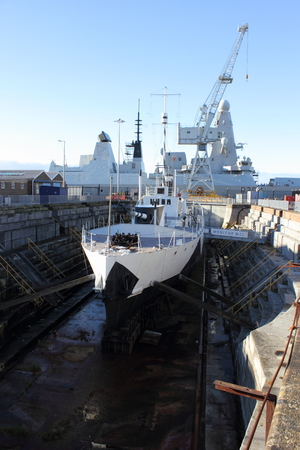 drydock: 1st world war ship M33 with the modern HMS dauntless in the Background Editorial