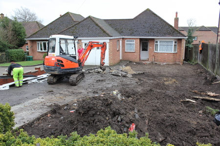 A mini digger being used in the preparation of groundwork for the laying of blockpaving Editorial