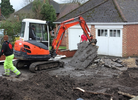 A mini digger being used in the preparation of groundwork for the laying of blockpaving