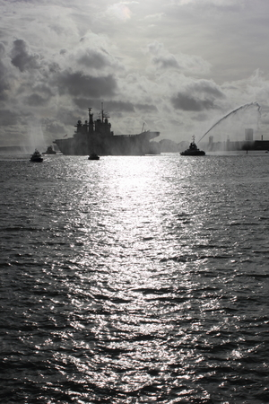 illustrious:  PORTSMOUTH, ENGLAND, 10TH JANUARY 2014  HMS Illustrious,the aircraft carrier returns to portsmouth after its deployment to the Philippines with a water canon salute from the tugboats, 10th january 2014