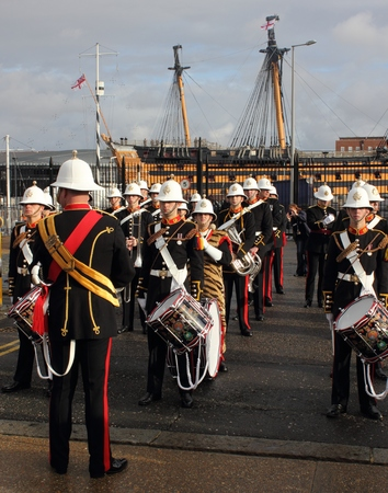 PORTSMOUTH, ENGLAND, 10TH JANUARY 2014 The Royal Marines marching band playing on the return of HMS Illustrious,the aircraft carrier to portsmouth after its deployment to the Philippines