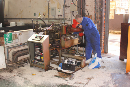 A Diesel fuel spill in a boilerhouse being cleaned by an engineer wearing his ppe using absorbent pads and granules soaking up and containing the spillage