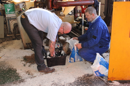 A Diesel fuel spill in a boilerhouse being cleaned by engineers with absorbent pads and granules soaking up and containing the spillage  Note, one engineer wearing ppe the other is not