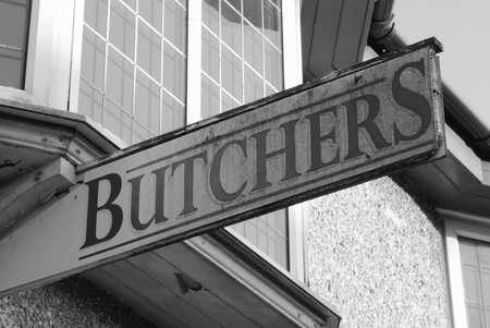 An old weathered Butchers sign hanging outside of a shop photo