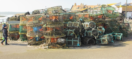 crab pots: AVON, HAMPSHIRE, ENGLAND 9TH MARCH 2014  Lobster and crab pots on the quayside with a young child at Avon in Hampshire on the 9th march 2014