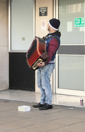 A busker playing his accordion on the streets of portsmouth, england 2014